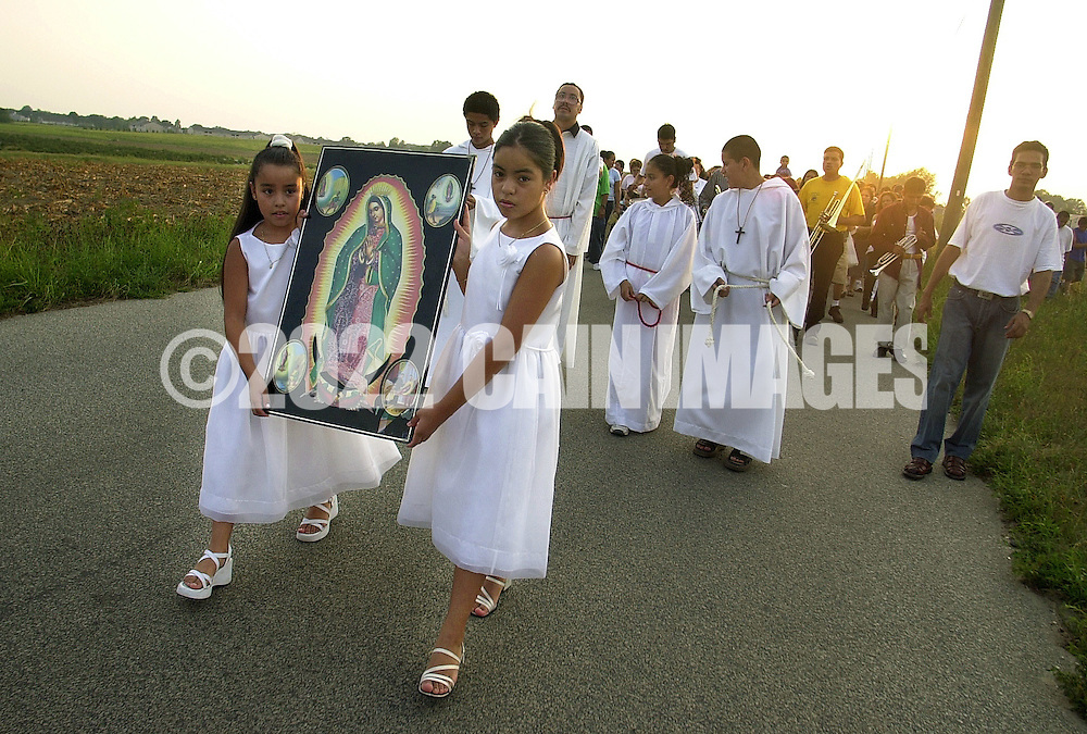 """HAMMONTON, NJ - AUGUST 19:  Dianne Castaneda (L), nine-years-old, and her sister Jazzalyn (C), eleven-years-old, carry a portrait of """"Our Lady of Guadalupe"""" during a procession leading to a Catholic mass, in a farm building, August 19, 2002, in Hammonton, New Jersey. Nearly 10,000 Mexican farm workers leave their homes to labor in the fields of South Jersey annually to harvest fresh vegetables. Farm workers labor from sunrise until dusk, harvesting, cultivating and packaging produce for fresh market sale with little time for anything else. The Diocese of Camden celebrates Mass in the fields to serve as """"a spiritual outreach"""" to the farm workers and their children. (Photo by William Thomas Cain/Getty Images)"""