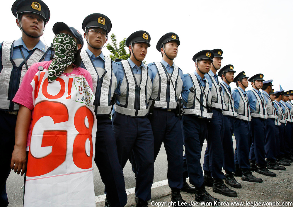 Police stand guard as anti-G8 summit protesters demonstrate in Sobetsu town, near the venue of the G8 Hokkaido Toyako Summit, on Japan's northern island of Hokkaido July 9, 2008. /Lee Jae-Won