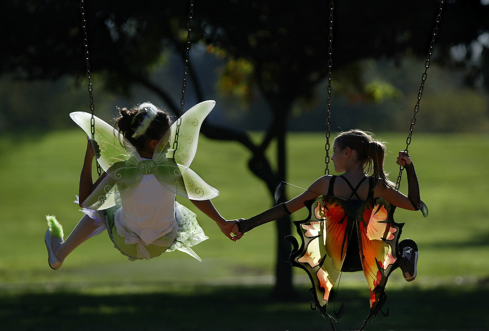 Butterflies are free to fly at Hagen Park as (left) Cori Guthrie 12 and her friend  (right) Hailey Harwell 11, enjoy a swing in their halloween costumes. The two of them live down the street from Hagen Park in Rancho Cordova and decided to bring their costumes out a day early for a late afternoon swing in the park.