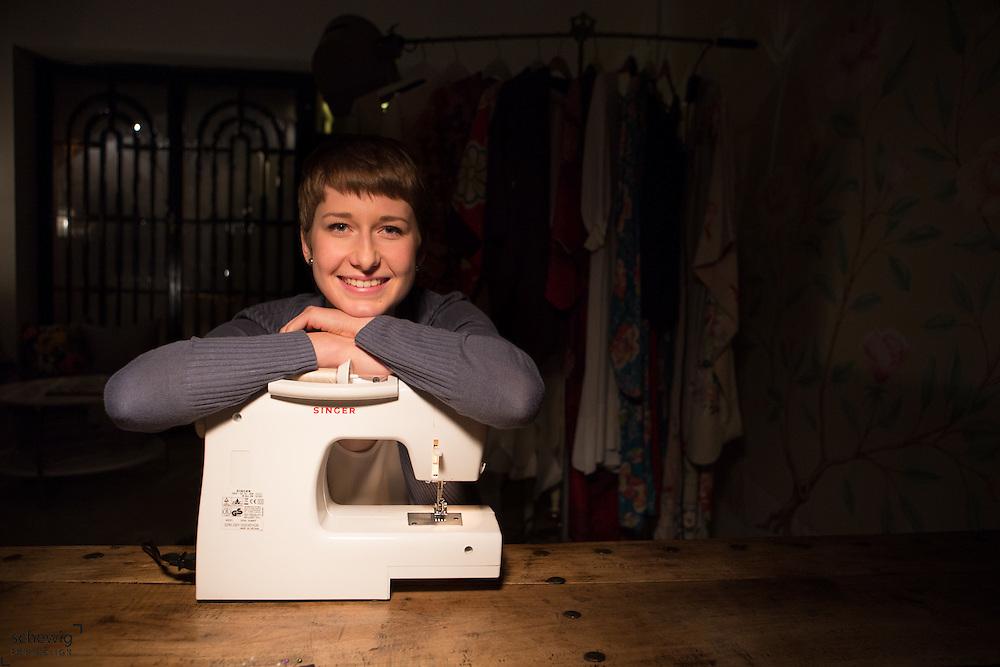 Junge Frau lehnt auf Nähmaschine in ihrem Workshop, Wien, Österreich, Jungunternehmerin im Kreativbereich, Portrait