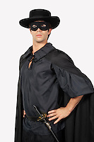Portrait of young man dressed as Zorro against gray background