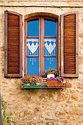 A window in a small Italian town with lace curtains and flowers.