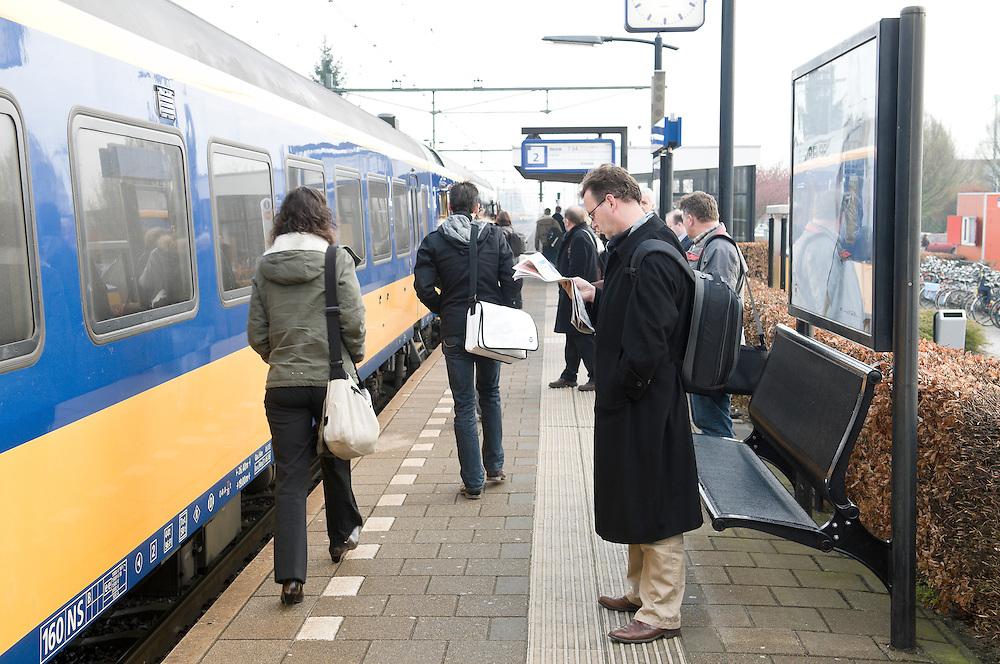 Nederland, Elst, 20080415..Station Elst. Reizigers staan te wachten op hun aansluiting. Trein is gestopt op het perron..Man leest de ochtendkrant.    .