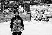 A local resident walks past a building decorated with posters of the films Die Hard and South Pacific in Yubari City, on the northernmost island of Hokkaido in Japan. The city, once well known for its international film festival, is today bankrupt.