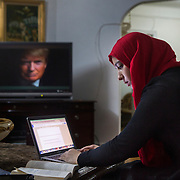 BRONX, NY - DECEMBER 10, 2015: Hebh Jamal, a 15-year-old Muslim, does homework at her family's home in the Bronx while a promotion for CNN's presidential debates flashes across the screen featuring an image of presidential candidate Donald J. Trump. CREDIT: Sam Hodgson for The New York Times.