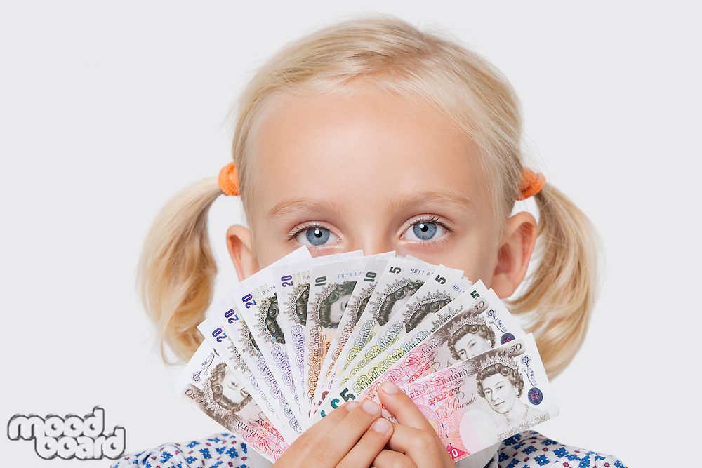 Portrait of a young girl covering mouth with fan of European currencies over white background