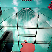 The Apple Logo, on the glass fronted Apple Store, surrounded by the high rise buildings of Manhattan opposite Central Park on Fifth Avenue, Manhattan, New York, USA.  Photo Tim Clayton<br /> Note to Editors. The color's of this image have been digitally altered in Photoshop.