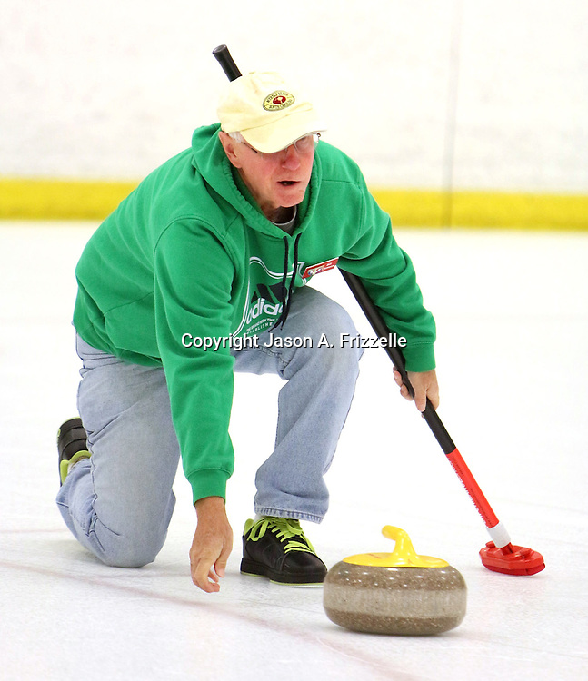 Bill Clawson delivers a stone during a curling match at the Wilmington Ice House. (Jason A. Frizzelle)