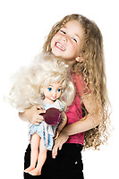 caucasian little girl portrait playing bonding  with a doll isolated studio on white background