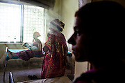 Laxmi Oli, 23, cradles her 3-day-old 2nd child, as her mother-in-law (center) looks on in the Bardia District Hospital one hour's walk from her village in Bardia, Western Nepal, on 29th June 2012. Laxmi had her first child at 18. In Bardia, StC works with the district health office to build the capacity of female community health workers who are on the frontline of health service provision like ante-natal and post-natal care, and working together against child marriage and teenage pregnancy especially in rural areas. Photo by Suzanne Lee for Save The Children UK