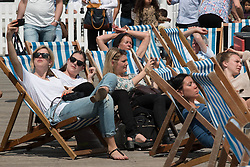 © Licensed to London News Pictures. 01/06/2014. Brighton, UK. A group of woman enjoy the sunshine on Brighton pier. Despite a good start to the weekend on Saturday the up and down weather has deterred some people from coming to the beach. Photo credit : Hugo Michiels/LNP