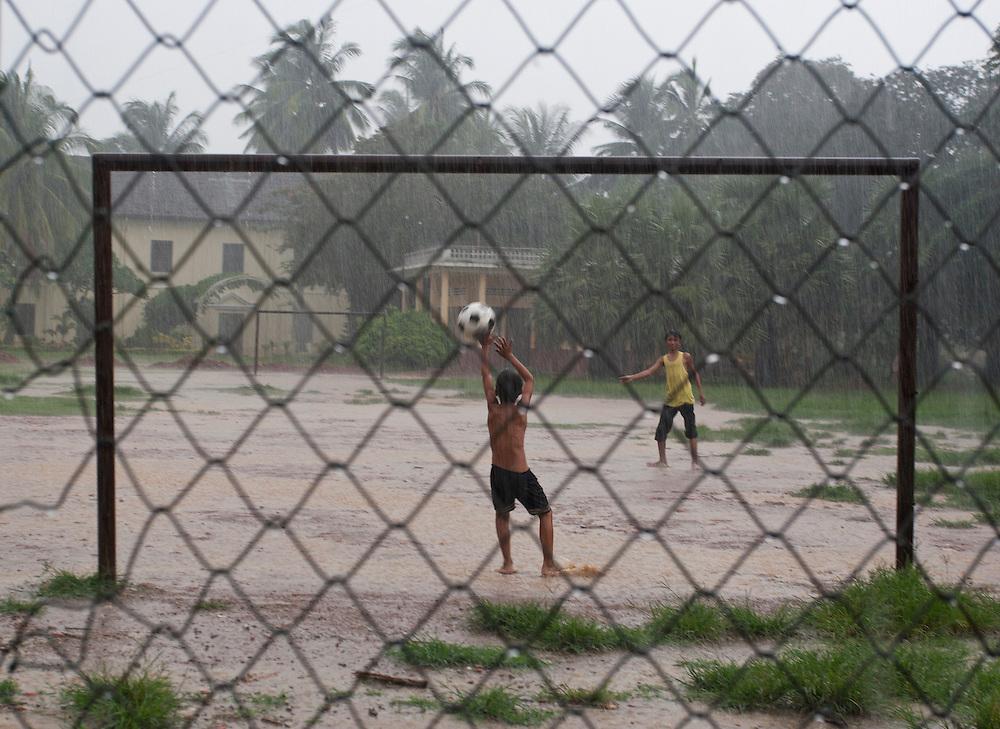 BATTAMBANG, CAMBODIA: Kids playing football under the rain at a pitch in Battambang, Cambodia.