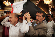 May 12, 2012-Damascus , Syria : At Al Outhman mosque men hold a coffin wrote on it in arabic ( parts of body for unknown person ) , during a funeral for the victims who died due a massive explosion targeted  al-Qazaz crowded intersection at the southern ring-road in Damascus .