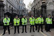 Police officers guard Downing Street as students protest outside parliament in Westminster, against spending cuts, tuition fees and student debt.