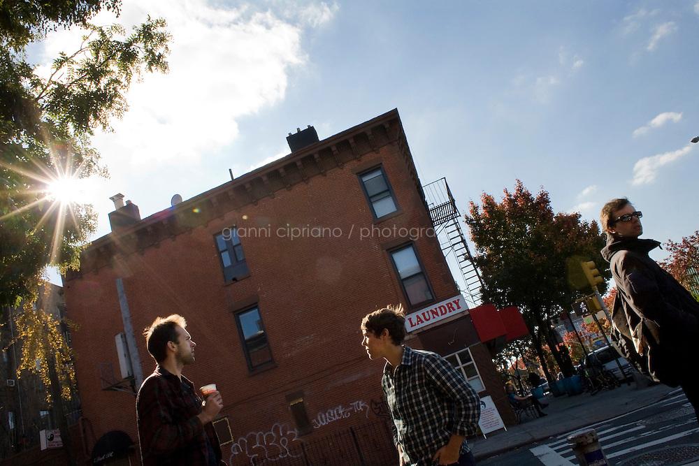 """7 Novembre, 2008. Brooklyn, New York.<br /> <br /> Dei ragazzi conversano vicino all'entrata della caffetteria Gorilla Coffee Inc., nella Fifth Avenue a Park Slope, Brookyln, New York. Park Slope, spesso definito dai newyorkesi come """"The Slope"""", è un quartiere nella zona ovest di Brooklyn, New York, e confinante con Prospect Park.  Park Slope è un quartiere benestante che ha il maggior numero di nascite, la qualità della vita più alta e principalmente abitato da una classe media di razza bianca. Per questi motivi molte giovani coppie e famiglie decidono di trasferirsi dalle altre municipalità di New York a Park Slope. Dal punto di vista architettonico, il quartiere è caratterizzato dai brownstones, un tipo di costruzione molto frequente a New York, e da Prospect Park.<br /> <br /> ©2008 Gianni Cipriano for The New York Times<br /> cell. +1 646 465 2168 (USA)<br /> cell. +1 328 567 7923 (Italy)<br /> gianni@giannicipriano.com<br /> www.giannicipriano.com"""