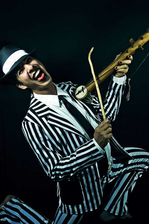 A young man dressed in a stripey suit playing a small stringed instrument