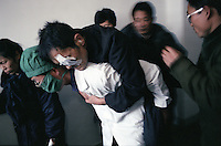 North Korea Eye Surgery Workshop. A elderly cataract patient is carried to surgery on the back of a North Korean doctor. The elderly generally suffer cataract blindness made worse by excessive reflected uv light, poor diet, and congenital reasons.