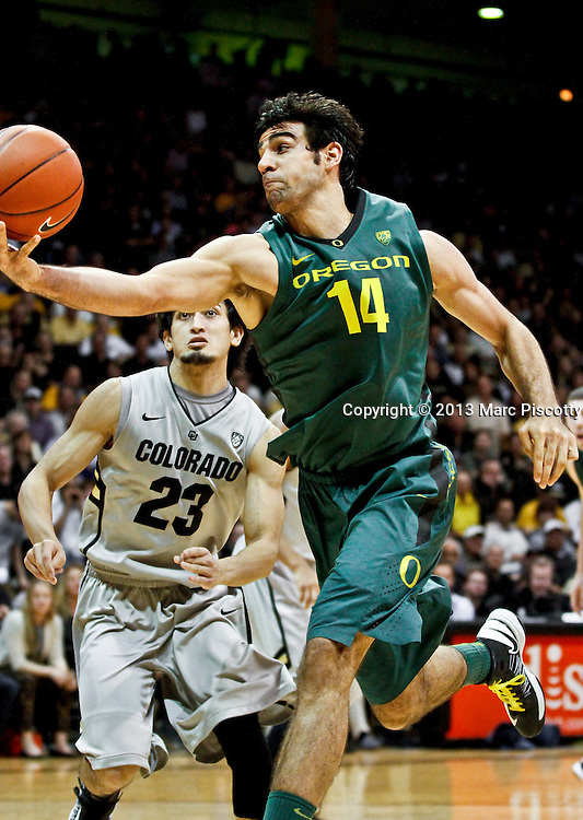 SHOT 3/7/13 9:40:25 PM - Oregon's Arsalan Kazemi #14 throws up a shot in front of Colorado's Sabatino Chen #23 during their Pac-12 Conference regular season basketball game at the Coors Events Center on the University of Colorado campus in Boulder, Co. Colorado won the game 76-53..(Photo by Marc Piscotty / © 2013)