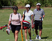 Fifteen year old Michelle Wie is flanked by her mother Bo and father BJ as she heads to the practice range prior to the 2005 SBS LPGA Women's Open at Turtle Bay Resort in Kahuku, Hawaii.