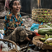 INDONESIA. Tulamben, Bali. June 2nd, 2013. Locals gather at the market to sell a mixture of fresh fruits, vegetables, produce and items to prepare the daily spiritual offerings.