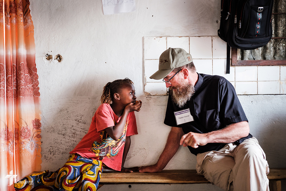The Rev. Daniel Mulholland, team chaplain and pastor of Shepherd of the Valley Lutheran Church, Fort Bridger, Wyo., chats with a young patient on the third day of the LCMS Mercy Medical Team on Wednesday, May 9, 2018, in the Yardu village outside Koidu, Sierra Leone, West Africa. LCMS Communications/Erik M. Lunsford