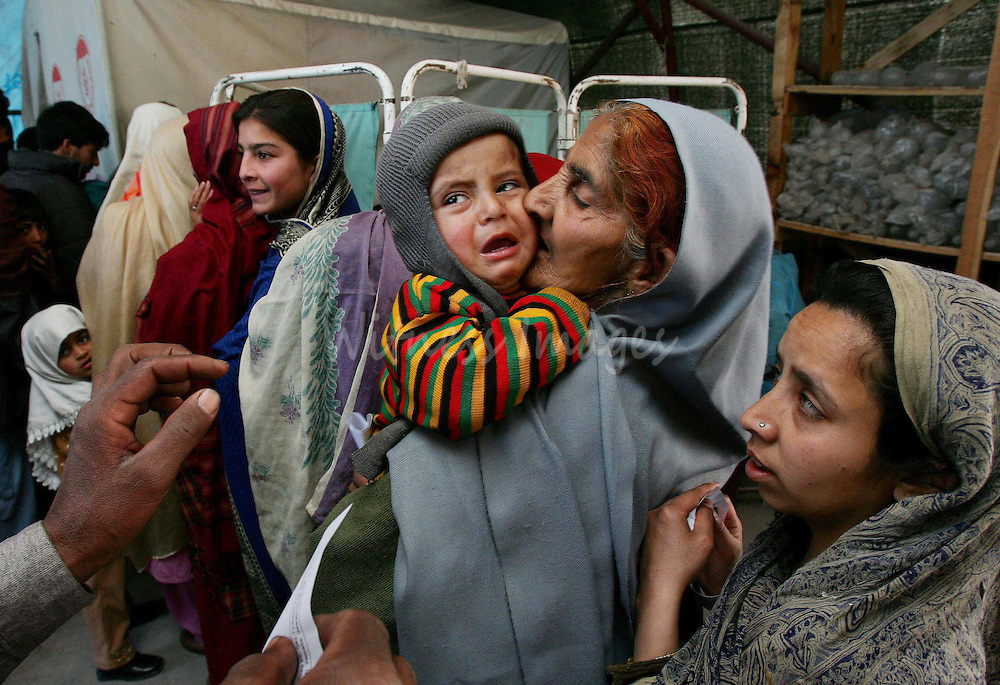 Kashmiri earthquake survivors wait for a doctor at the Aldawa field hospital in the earthquake-devastated city of Muzaffarabad in Pakistan-administered Kashmir February 23, 2006. Winter weather has made life more difficult for survivors of last year massive earthquake in South Asia where more than two million people have been living in tents or crude shelters patched together from ruined homes. REUTERS/Thierry Roge