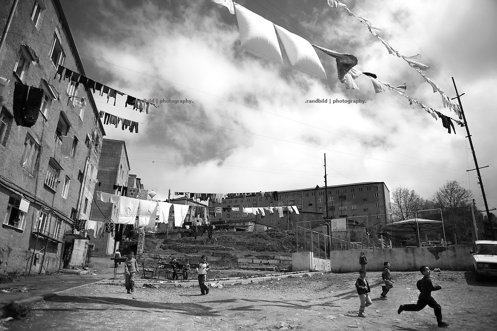 """Boys playing in a courtyard of Shushi residential houses. This image is part of the photoproject """"The Twentieth Spring"""", a portrait of caucasian town Shushi 20 years after its so called """"Liberation"""" by armenian fighters. In its more than two centuries old history Shushi was ruled by different powers like armeniens, persians, russian or aseris. In 1991 a fierce battle for Karabakhs independence from Azerbaijan began. During the breakdown of Sowjet Union armenians didn´t want to stay within the Republic of Azerbaijan anymore. 1992 armenians manage to takeover """"ancient armenian Shushi"""" and pushed out remained aseris forces which had operate a rocket base there. Since then Shushi became an """"armenian town"""" again. Today, 20 yeras after statement of Karabakhs independence Shushi tries to find it´s opportunities for it´s future. The less populated town is still affected by devastation and ruins by it´s violent history. Life is mostly a daily struggle for the inhabitants to get expenses covered, caused by a lack of jobs and almost no perspective for a sustainable economic development. Shushi depends on donations by diaspora armenians. On the other hand those donations have made it possible to rebuild a cultural centre, recover new asphalt roads and other infrastructure. 20 years after Shushis fall into armenian hands Babies get born and people won´t never be under aseris rule again. The bloody early 1990´s civil war has moved into the trenches of the frontline 20 kilometer away from Shushi where it stuck since 1994. The karabakh conflict is still not solved and could turn to an open war every day. Nonetheless life goes on on the south caucasian rocky tip above mountainious region of Karabakh where Shushi enthrones ever since centuries."""