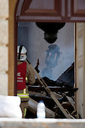 © Licensed to London News Pictures. 30/04/2015. Surrey, UK. Damage to the house can bee seen through windows and doors. Fire officers at the scene of the fire today 30 April 2015. A fire at the National Trust-run Clandon Park House, near Guildford, is thought to have started in the basement just after 16:00 BST on Wednesday. Photo credit : Stephen Simpson/LNP