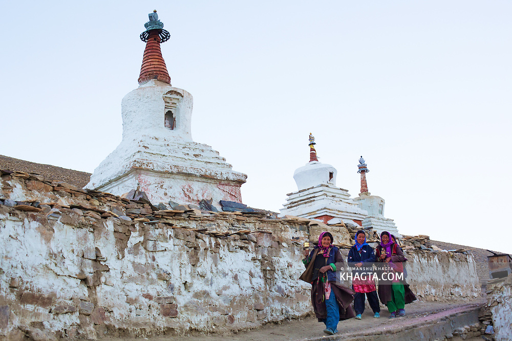 Three Ladakhi ladies walking past the ancient Chortens in Korzok village of Ladakh.