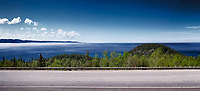Panorama of Trans-Canada highway with blue sky over misty Lake Superior nature scenery in the background. Ontario, Canada.