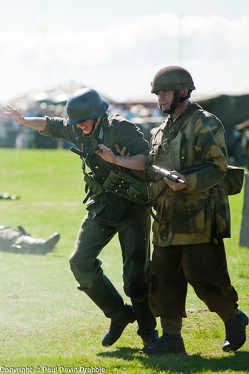 Sunday 18th August 2012 Lytham Saint Annes .A paratrooper of the 6th Airborne Division brings in a captured German Panzergrenadier from 1 Kompanie GrossDeutschland during Saturdays battle reenactment on Lytham Green, both are renactors from the Northern World War Two Association (NWW2A) ..18 August 2012.Image © Paul David Drabble