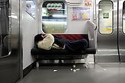 A homeless man sleeps on a train in Tokyo, Japan.