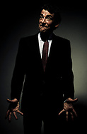 Front view of a mature man in a business suit, looking to the side, with palms flung open in frustration at his sides in Santa Barbara, California.  Three quarter length studio shot against a dark background. (releasecode: jk_mr1025) (Model Released)