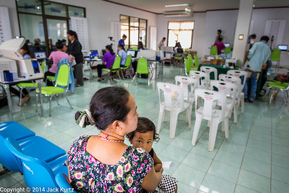 09 JULY 2014 - ARANYAPRATHET, SA KAEO, THAILAND:  A Cambodian woman and her child in the waiting area at the Thai Immigration One Stop Service Center in Aranyaprathet on the Thai-Cambodian border. More than 200,000 Cambodian migrant workers, most undocumented, fled Thailand in early June fearing a crackdown by Thai authorities after a coup unseated the elected government. Employers have been unable to fill the vacancies created by the Cambodian exodus and the Thai government has allowed them to return. The Cambodian workers have to have a job and their employers have to vouch for them. The Thai government is issuing temporary ID cards to allow them to travel openly to their jobs. About 800 Cambodian workers came back to Thailand through the Aranyaprathet border crossing Wednesday. The Thai government has opening similar service centers at three other crossing points on the Thai-Cambodian border.   PHOTO BY JACK KURTZ