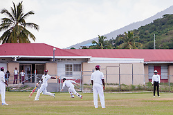 Kevin McClean of Windward Islands Volcanoes (left) looks for a run as Leeward Islands Hurricanes wicketkeeper Jahmar Hamilton chases down the ball during play on the final day of the seventh round match in the WICB Professional Cricket League Regional 4-Day Tournament at Addelita Cancryn Junior High School.  22 February 2016.  St. Thomas, VI.  © Aisha-Zakiya Boyd