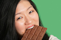 Close-up portrait of a young woman eating chocolate over green background