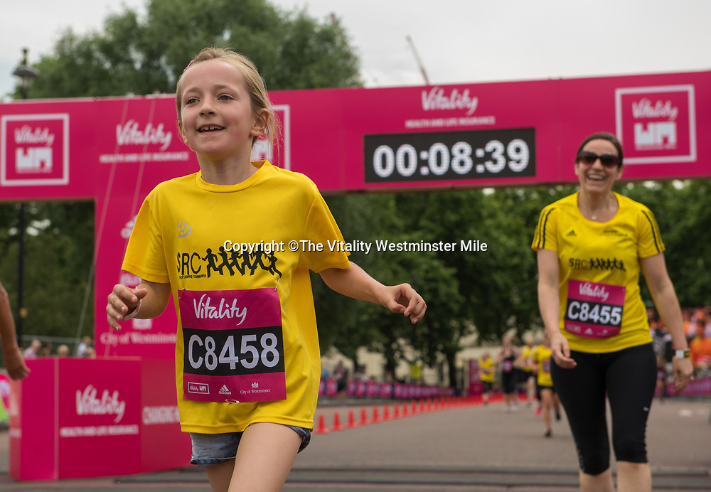 Runners from the Sweatshop wave at the finishing line outside Buckingham Palace at The Vitality Westminster Mile, Sunday 28th May 2017.<br /> <br /> Photo: Thomas Lovelock for The Vitality Westminster Mile<br /> <br /> For further information: media@londonmarathonevents.co.uk
