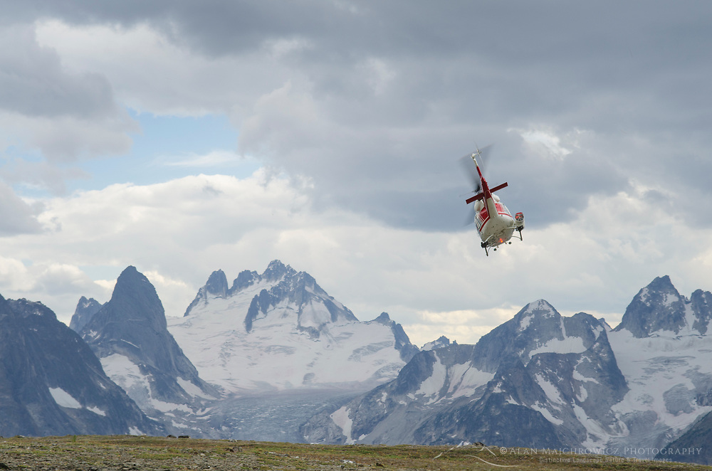 Helicopter lifting off Rocky Point Ridge, Bugaboos in the distance. Bugaboo Provincial Park, Purcell Mountains British Columbia.