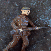 Worn lead model of World War 1 army foot soldier running with rifle at waist level against mottled metal background