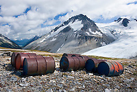 Fuel drums abandoned by miners and left to rust and leak into the wilderness watershed of Salal Creek, Mount Ethelweard 2819 m (9249 ft) is in the distance. Coast Mountains British Columbia