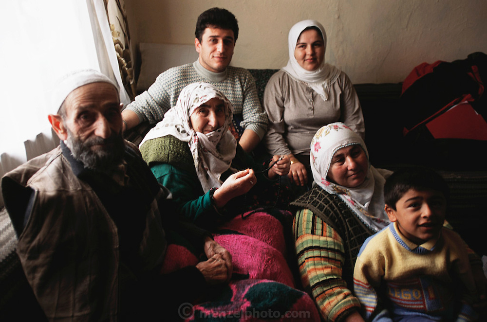 Çinar Family of Golden Horn (or Haliç) area, Istanbul, Turkey. At center, back is Sezgi Çinar, 30 and his wife Feriye, 28 (mother of Hasan, 8, foreground, and Saliç, 11, not in photo). In front of Feriye is her mother-in-law Safiye, 55. Safiye's parents, at left are Emine, 78, and Mehmet, 81. Safiye's husband Hasan, 60, is not in photo. Material World project.