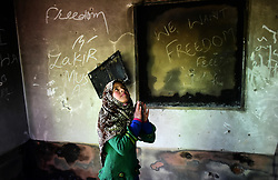 March 22, 2019 - Srinagar, Kashmir, India - A Kashmiri girl asses the damaged residential house which was damaged in a gunfight between Indian Government forces and suspected foreigner Militants in Hajin area of Bandipora district, Indian Administered Kashmir on 22 March 2019. Indian government forces have killed 8 rebels in 4 separate gunfights across Kashmir. Two foreign militants and a minor civilian boy was killed during the encounter. (Credit Image: © Muzamil Mattoo/NurPhoto via ZUMA Press)