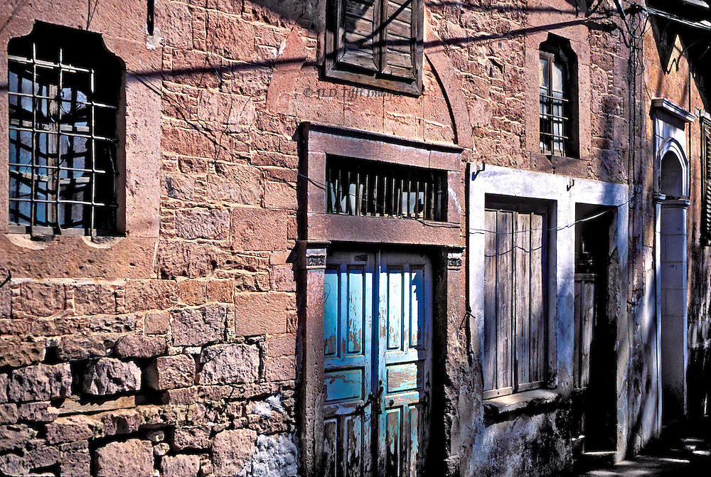 Intense sunlight and a festoon of shadows from electric wiring characterize the facade of a stone house.  Barred window, painted wooden door, and a sense that the house is being kept if not lived in.