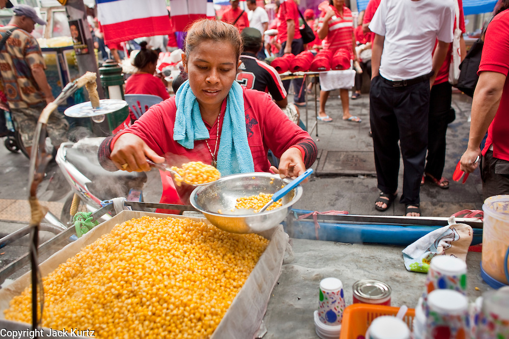 17 APRIL 2010 - BANGKOK, THAILAND: A corn vendor sells a snack to a Red Shirt in Ratchaprasong Intersection. A whole economy has sprung up around the Red Shirt camp with vendors selling everything from snacks and meals to mats (that they sit on) to fans, hats and Red Shirt souvenirs. The Red Shirts continue to occupy Ratchaprasong Intersection an the high end shopping district of Bangkok. They are calling for Thai Prime Minister Abhisit Vejjajiva to step down and dissolve the parliament. Most of the Red Shirts support ousted former Prime Minister Thaksin Shinawatra.   PHOTO BY JACK KURTZ