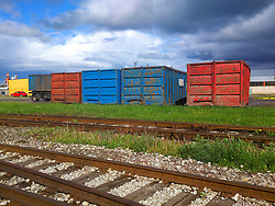 Large colorful metal containers by railway. Transportation, metals. Rails, cargo.