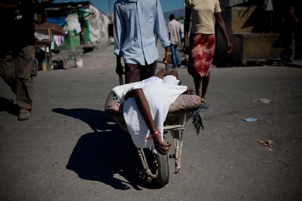 Durante la segunda quincena del mes de Octubre de 2010 comenzaron a aparecer casos de C&oacute;lera en la regi&oacute;n de Artibonite, en Hait&iacute;. Desde entonces la epidemia ha dejado m&aacute;s de 4.500 muertos y cerca de 250.000 afectados.<br /> <br /> A man carries a woman suffering cholera symptoms in a wheelbarrow as they arrive to the St Catherine Hospital in Cite Soleil slum in Port au Prince (Haiti). Wheelbarrows have became the best way to carry ill people for the poorest that don't have another way or money to contract a transport.<br /> <br /> Andr&eacute;s Mart&iacute;nez Casares/EFE