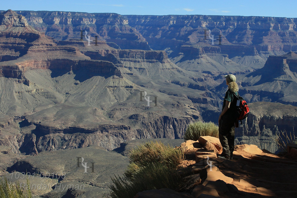 Woman hiker pauses along South Kaibab Trail near Cedar Ridge to enjoy sweeping view of Grand Canyon National Park, Arizona.