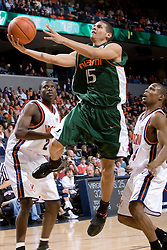 Miami Hurricanes guard Denis Clemente (15)goes up for a shot around Virginia Cavaliers point guard Sean Singletary (44) and Virginia Cavaliers guard/forward Mamadi Diane (24).  The University of Virginia Cavaliers defeated the Miami Hurricanes Men's Basketball Team 81-70 at the John Paul Jones Arena in Charlottesville, VA on February 3, 2007.