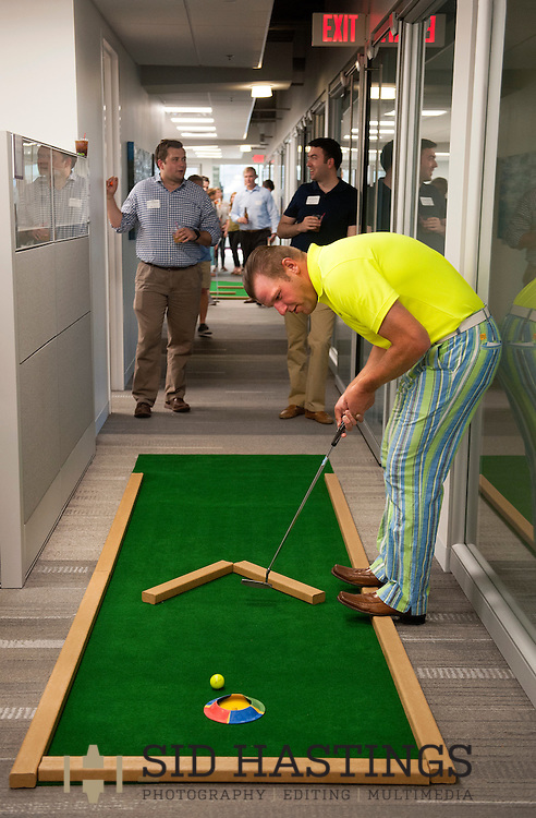 2 JUNE 2016 -- ST. LOUIS -- Steve Rommerskirchen of Anders CPAs + Advisors prepares to putt on the putt-putt course laid out among the offices at the company in downtown St. Louis as part of Putt and Prosper 2016 Thursday, June 2, 2016. An after work happy hour sponsored by Anders' Young Professional Group for employees, customers and friends, Putt and Prosper scattered putt-putt holes throughout the firm's offices and raised funds for Stray Rescue of St. Louis. Photo © copyright 2016 Sid Hastings.