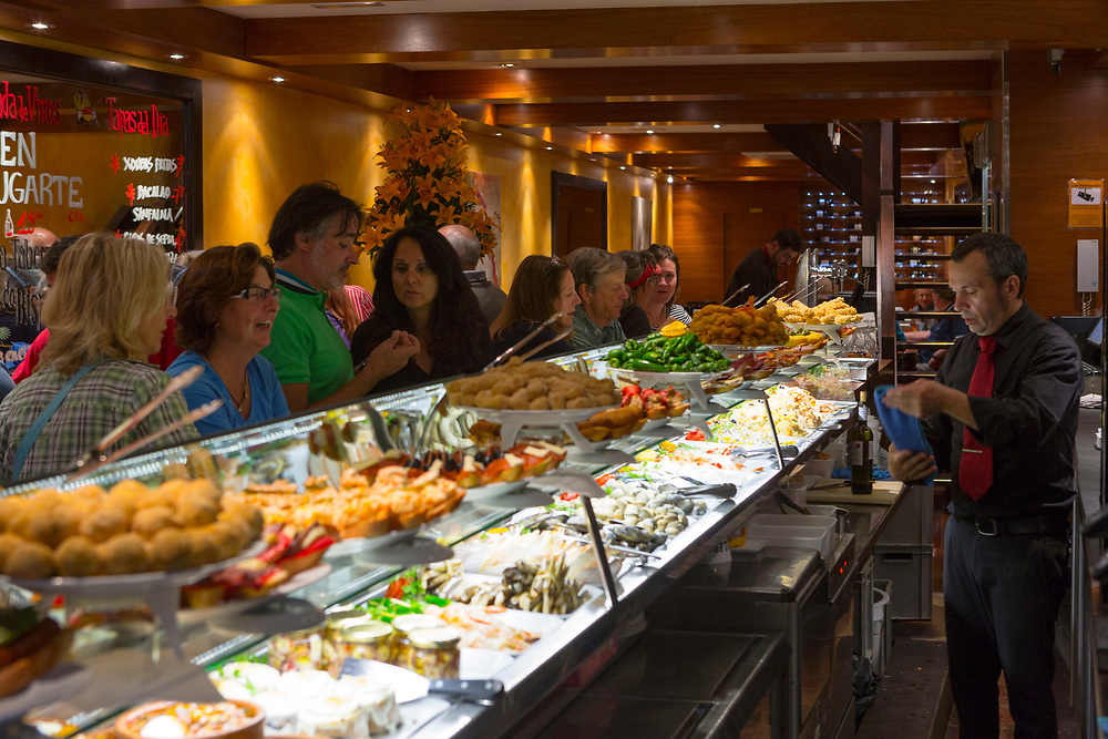 SANTIAGO DE COMPOSTELA, SPAIN - 11th of October - Tourists enjoy sampling local cuisine at a tapas bar in Santiago de Compostela, Galicia, Spain.